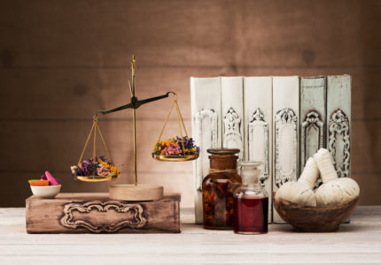 Herbal Chinese medicine concept. Body care and aromatherapy. Scales with dried herbs, recipe books, herbal massage balls and incense sticks